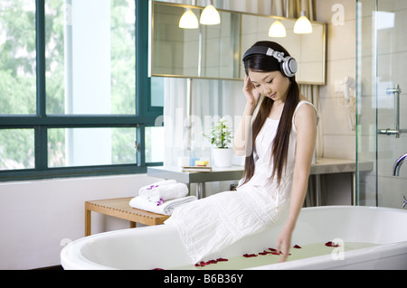 Young woman sitting on the bathtub and wearing the headphone - Stock Photo