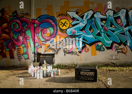 Graffiti art and Spray cans in an Alley - Stock Photo
