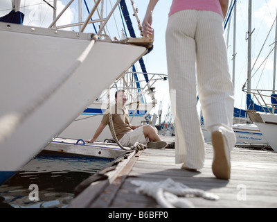 Man looking at woman walking on pier - Stock Photo