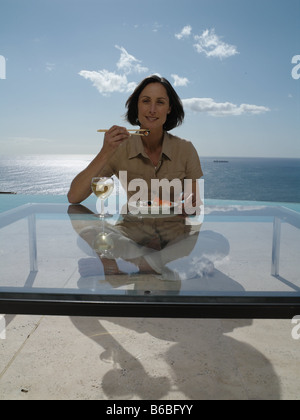Portrait of woman having food at table - Stock Photo
