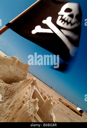 Pirate flag fluttering on beach - Stock Photo