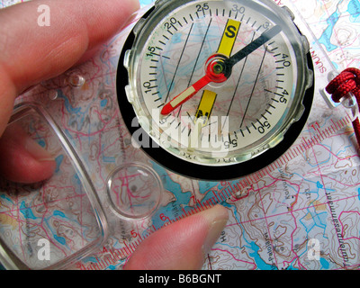 Close-up of person holding compass over map - Stock Photo