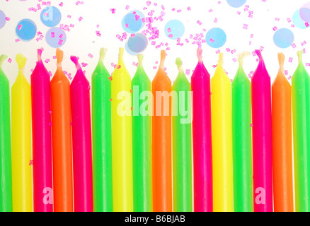 Row of unlit birthday candles with confetti and cake sprinkles - Stock Photo