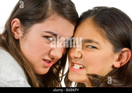 Horizontal close up portrait of two teenage sisters snarling menacingly during a fight against a white background - Stock Photo