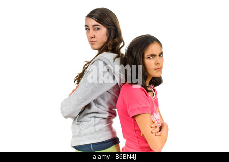 Horizontal close up portrait of two teenage sisters standing back to back staring menacingly against a white background. - Stock Photo