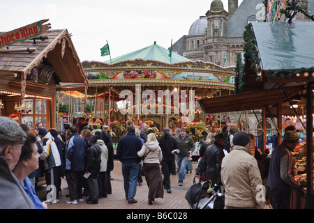 A Busy Christmas Market in Birmingham, with a Roundabout in the background - Stock Photo