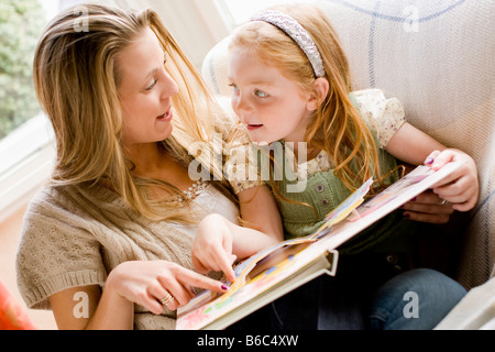 mother reading a book with her daughter - Stock Photo
