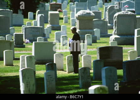 Mature Woman with US flag in cemetery - Stock Photo