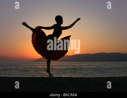 Dramatic image of a woman dancing by the ocean at sunset silhouette - Stock Photo