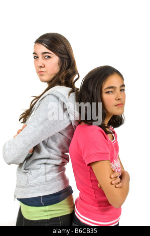 Vetical close up portrait of two teenage sisters standing back to back staring menacingly against a white background. - Stock Photo