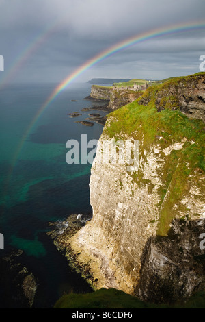 A double rainbow over the cliffs at White Rocks and view towards Dunluce Castle on the North Antrim coast, Northern Ireland