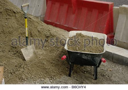 Shovel spade wheelbarrow sand London England Street road building digging hole construction tool tools - Stock Photo