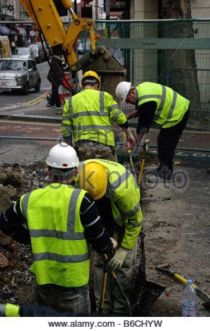 CONSTRUCTION London England digging the roads road dig workers men male street repair repairing maintenance workmen - Stock Photo