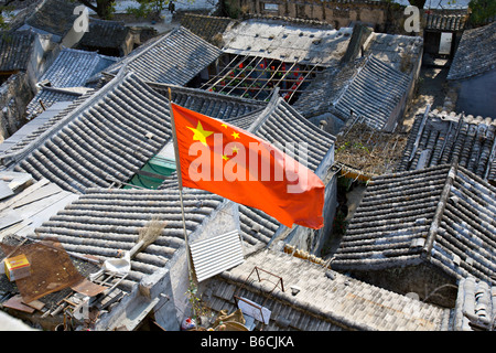 CHINA Chuandixia Flag of the Peoples Republic of China flying above the tile rooftops of traditional stone communal - Stock Photo