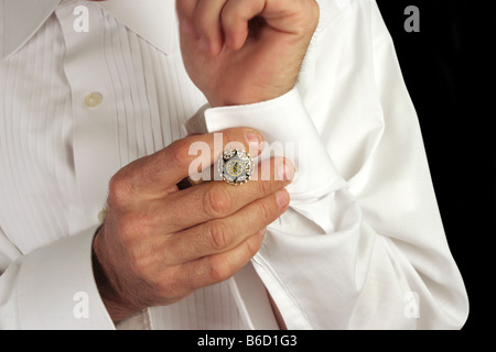 A man putting on antique cufflinks as he gets dressed in formal wear - Stock Photo