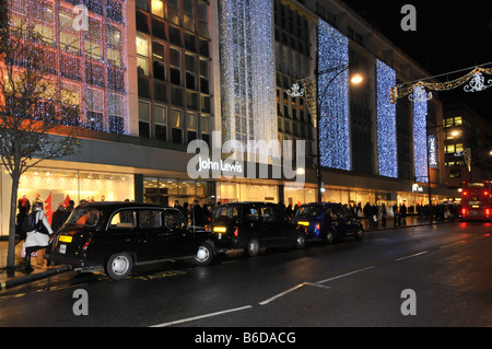 John Lewis department store Oxford street with Christmas lights and traffic - Stock Photo