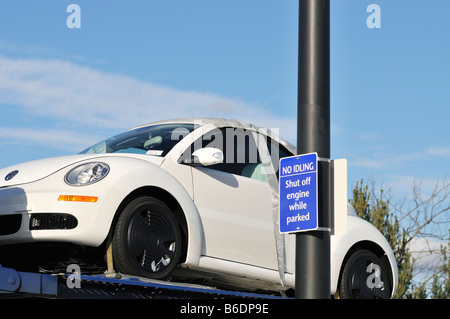 VW Beetle on car transport carrier parked next to sign 'no idling, shut off engine while parked'. USA - Stock Photo