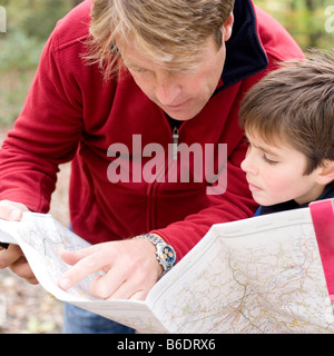 Father and son reading a map. The father is pointing to a location on the map. - Stock Photo
