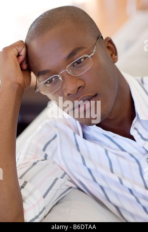 Depression. Unhappy man wearing glasses resting his head on his hand. - Stock Photo