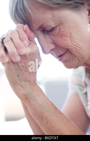 a woman holding her hand on her forehead feeling ill with ...