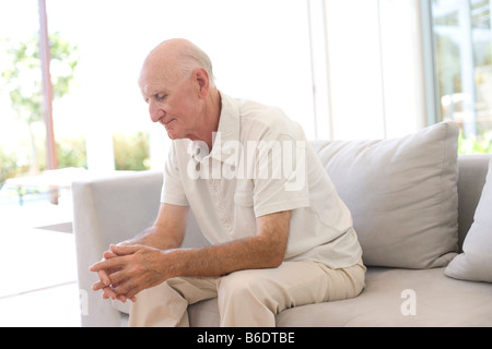 Loneliness. Man sitting alone on a sofa. - Stock Photo