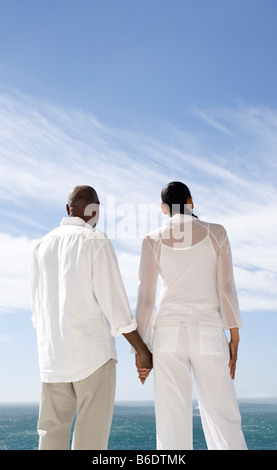 Happy senior couple holding hands and looking out to sea.