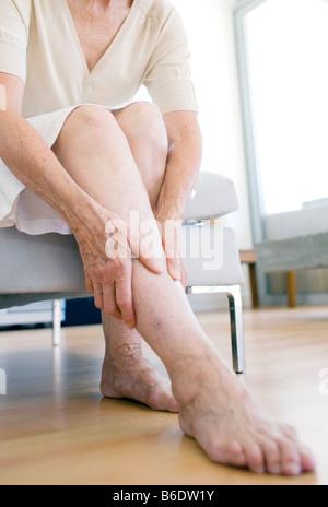 Woman rubbing her aching leg - Stock Photo