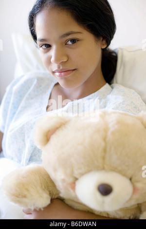 Teenage hospital patient. Teenagegirl cuddling a teddy bear in a hospital bed. - Stock Photo