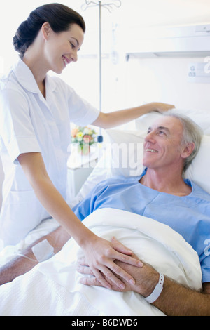 Patient care. Nurse reassuring a patient on a hospital ward. - Stock Photo