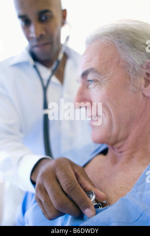 Hospital examination. Doctor using a stethoscope to listen to a patient's chest. - Stock Photo