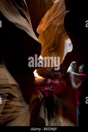 A tourist winds through Upper Antelope Canyon (Tse Bighanilini'), Page, Arizona. - Stock Photo