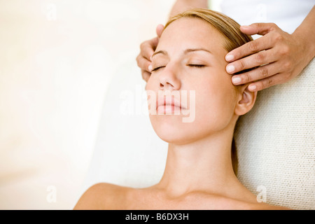 Woman receiving temple massage which can relieve muscular pain or stiffness by stimulating blood flow to affected - Stock Photo