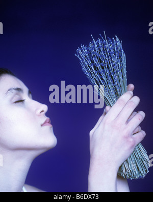 Young woman inhaling aroma of lavender flowers - Stock Photo