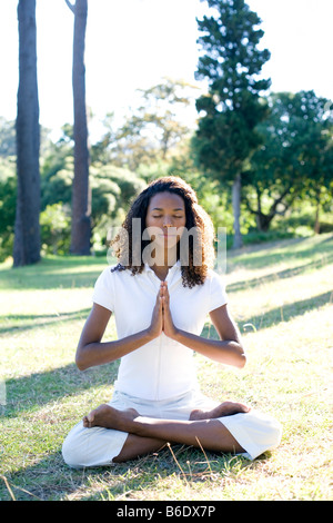 Young woman meditating in lotus position - Stock Photo