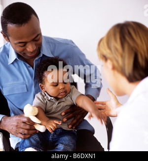 Paediatric examination. Doctor examining a 5-month-old boy sitting in his father's lap. - Stock Photo