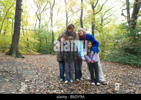 Parents and children in a wood in autumn. - Stock Photo