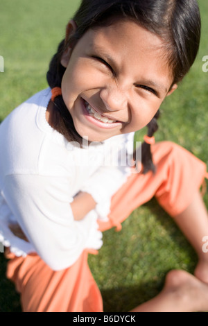 Smiling girl sitting on grass. - Stock Photo