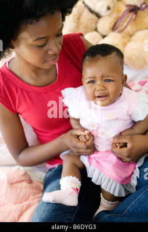 Teenage mother and baby. Four month old baby girl crying on her mother's knee. Posed by models. - Stock Photo