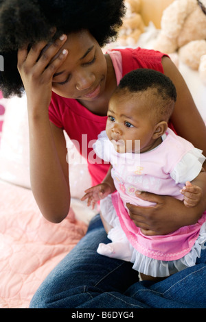 Teenage mother and baby. Stressed young mother holding her 4 month old daughter. - Stock Photo