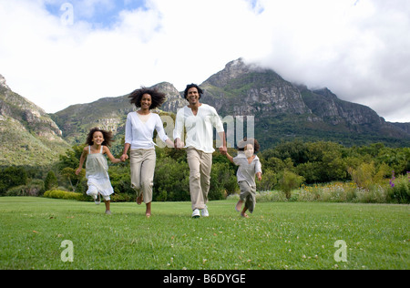 Happy family. Parents running with their two children in the countryside. - Stock Photo