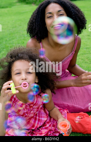 Mother and daughter sitting together on the grass blowing soap bubbles. - Stock Photo