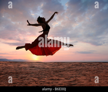 Dramatic image of a woman jumping above the ocean at sunset silhouette - Stock Photo