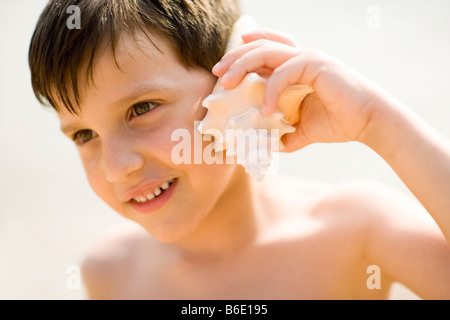 Boy holding seashell by his ears - Stock Photo