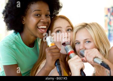 Karaoke. Teenage girls singing into microphones. - Stock Photo