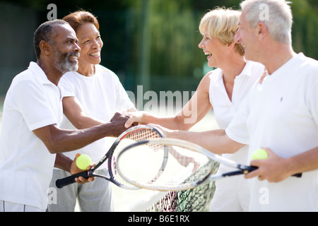Tennis players shaking hands after a doubles match. - Stock Photo