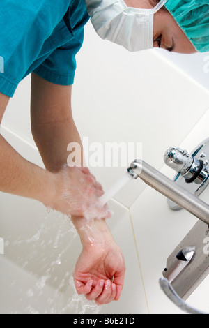 Scrubbing up. Surgeon cleaning herhands before surgery - Stock Photo