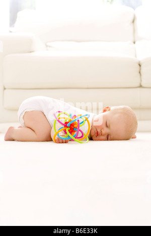 Baby girl (6-11 months)sleeping on the floor with a toy in her hand - Stock Photo