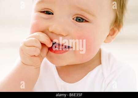 Baby boy (6-11) chewing thumb, close-up - Stock Photo