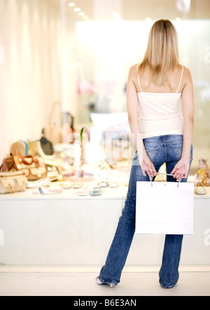 Woman looking at shoes in shop window - Stock Photo