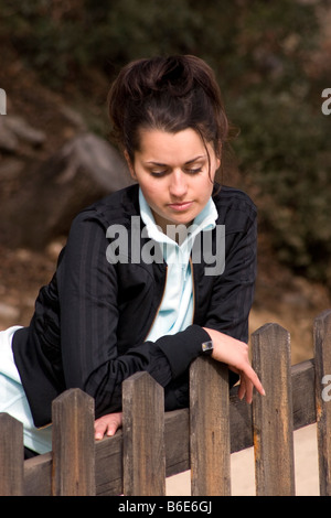 portrait unhappy looking young woman standing by fence - Stock Photo